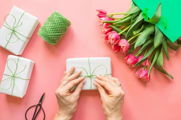 Frische rote tulpenblumen in der grünen papiertüte auf rosa.
