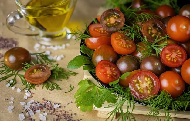 Frische rote und burgunderrote kirschtomaten auf einem schwarzen teller auf dem tisch mit dill und petersilie