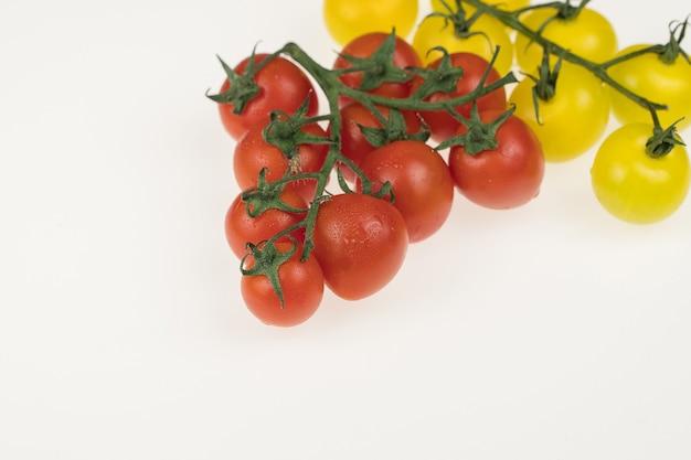 Frische rote und gelbe kirschtomaten auf weißem hintergrund. nasse tomaten