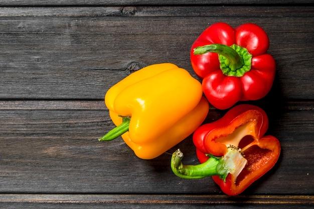 Frische rote und gelbe paprika. auf hölzernem hintergrund
