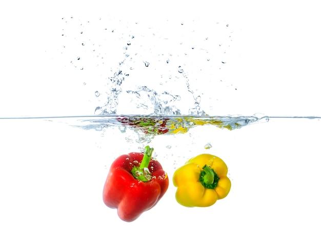 Frische rote und gelbe paprika-früchte spritzen im wasser