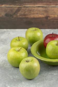 Frische rote und grüne äpfel in grüner schüssel auf marmor.