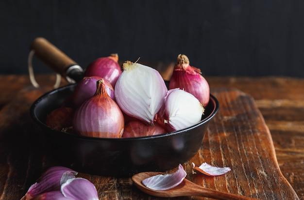 Frische rote zwiebeln in der pfanne auf dem küchentisch