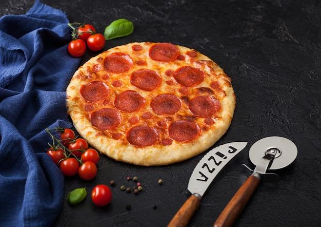 Frische rund gebackene italienische pepperonipizza mit radschneider und messer mit tomaten und basilikum auf schwarzem küchentischhintergrund.