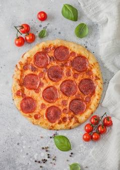 Frische, rund gebackene italienische pepperonipizza mit tomaten mit basilikum auf hellem küchentischhintergrund. platz für text