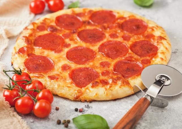 Frische runde gebackene italienische pepperoni-pizza mit radschneider, tomaten und basilikum