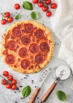 Frische runde gebackene italienische pepperoni-pizza mit radschneider und messer mit tomaten und basilikum