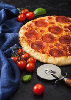 Frische runde gebackene italienische pepperoni-pizza mit radschneider und tomaten mit basilikum