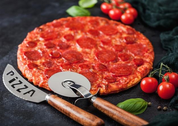 Frische runde gebackene scharfe und würzige pepperoni-pizza mit radschneider und messer mit tomaten und basilikum auf schwarzem küchentischhintergrund.