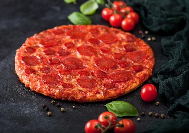 Frische runde gebackene scharfe und würzige pepperoni-pizza mit tomaten mit basilikum auf schwarzem küchentischhintergrund.