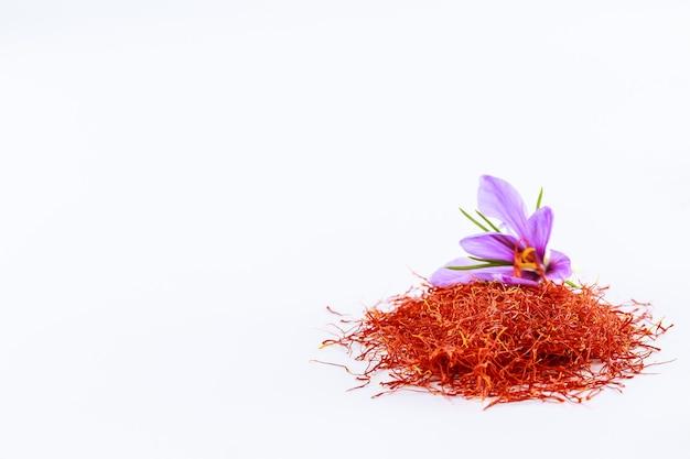Frische safranblume auf einem hintergrund des getrockneten safrans auf einem tisch. platz für ihren text