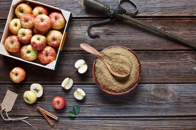 Frische saftige äpfel in holzkiste, steelyard, braunem zucker und zimtstangen