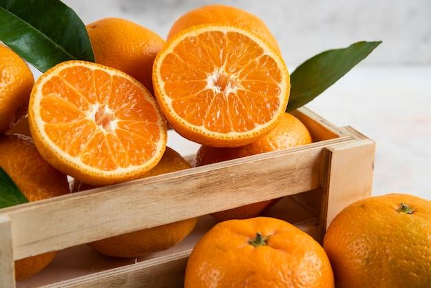 Frische saftige clementine in holzkiste. ganz oder halb geschnitten