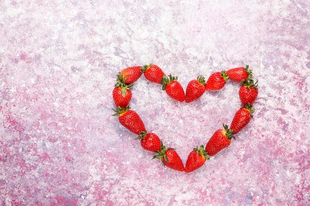Frische saftige erdbeeren auf hellem hintergrund, draufsicht