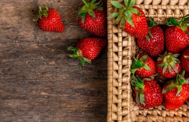 Frische saftige erdbeeren im korb. weidenkorb voll frisch gepflückter erdbeeren auf weinlesehintergrund