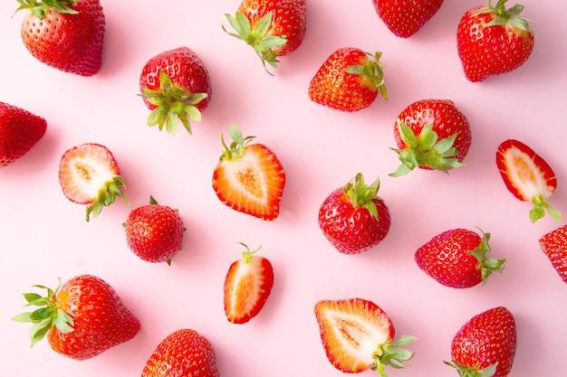 Frische saftige erdbeeren tragen auf rosa hintergrund früchte. obst hintergrund. ansicht von oben, flach. abstrakte erdbeere