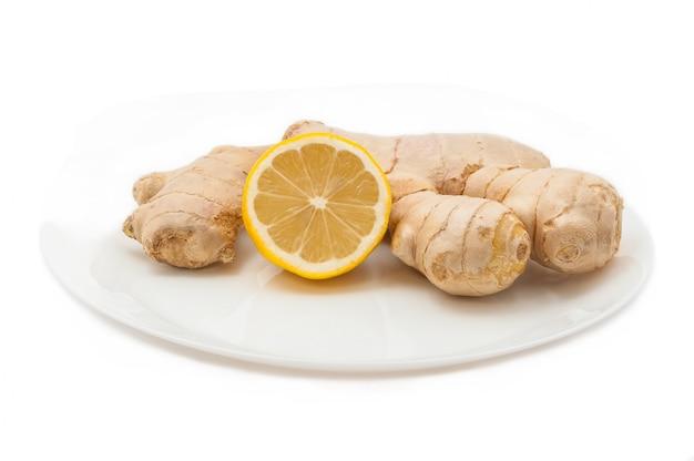 Frische saftige gelbe zitrone mit ingwer auf einer weißen platte lokalisiert.