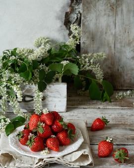 Frische saftige organische erdbeeren auf einer alten hölzernen strukturierten tabelle