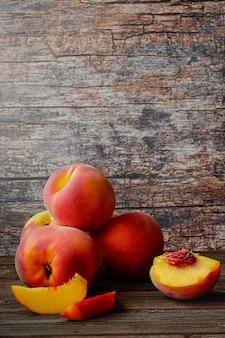 Frische saftige pfirsiche auf dunklem rustikalem hintergrund kopieren sie raum