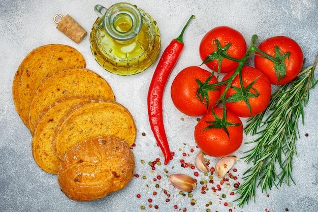Frische saftige reife tomaten auf einer niederlassung, einem roten pfeffer, einem rosmarin, einem knoblauch und gewürzen