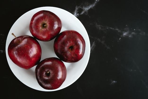 Frische saftige rote äpfel auf weißer platte auf schwarzer marmoroberfläche. draufsicht flach legen zusammensetzung. platz für textvorlage