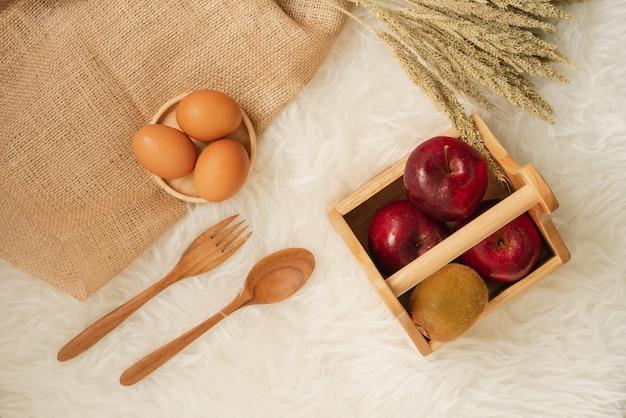 Frische saftige rote äpfel und kiwi im hölzernen korb mit eiern auf hölzernem untersetzer- und leinwandstoff