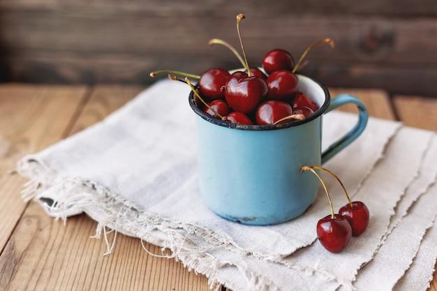 Frische saftige süße kirschen im alten rostigen becher