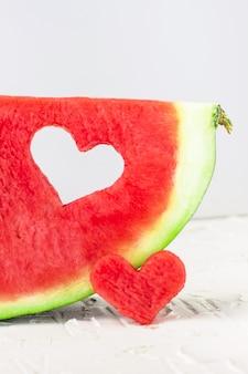 Frische saftige wassermelonenscheibe mit herzformloch auf weiß