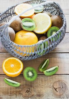 Frische saftige zitrusfrüchte in einem korb auf holz