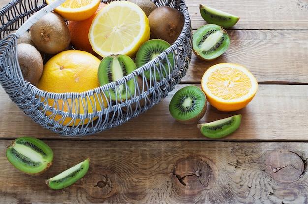 Frische saftige zitrusfrüchte in einem korb auf holzoberfläche