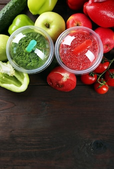 Frische saftmischungsfrucht, gesunde getränke in plastikbechern auf hölzernem hintergrund