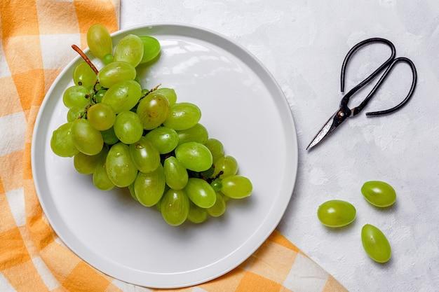 Frische saisonale trauben in plastikteller mit schere