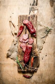 Frische salami mit gewürzen, pfeffer und knoblauch. auf holzoberfläche.