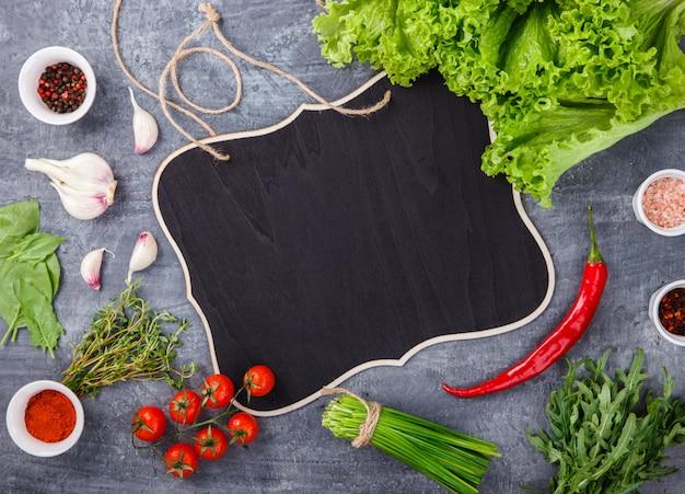 Frische salatgrüns des kopfsalates mit gewürzen und frischgemüse. vegetarier