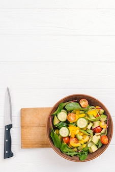 Frische salatschüssel auf hackendem brett mit scharfem messer auf weißer tabelle