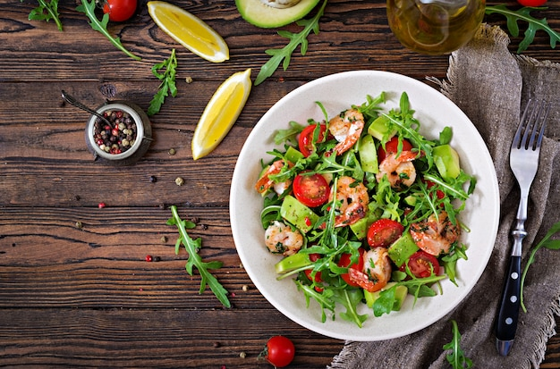 Frische salatschüssel mit garnelen, tomaten, avocado und rucola auf holztisch schließen oben. gesundes essen. sauberes essen. draufsicht. flach liegen.