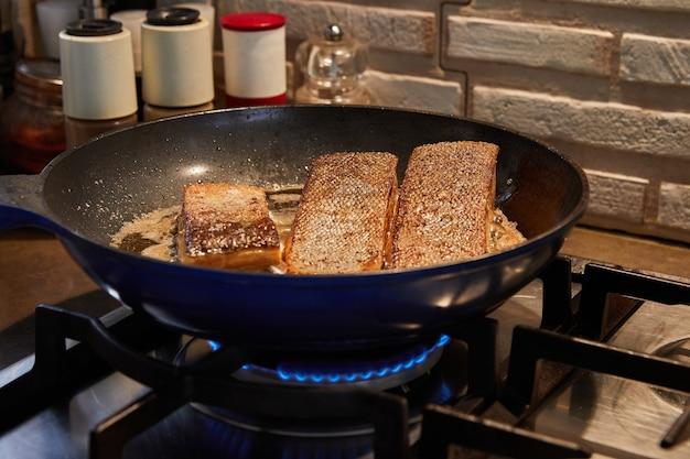Frische salomon-fischfilets werden in der pfanne auf dem gasherd gebraten