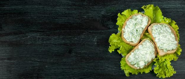 Frische sandwiche mit gemüse auf einem dunklen brett auf einer strukturierten oberfläche.