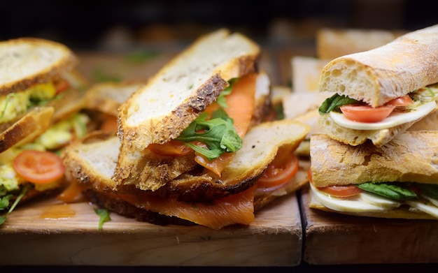 Frische sandwiches auf hölzernem schneidebrett im schaufensterbummel des cafés oder des restaurants