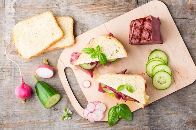 Frische sandwiches mit pastrami, gurke und rettich auf einem schneidebrett. amerikanischer imbiss. rustikaler stil.. ansicht von oben