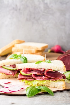 Frische sandwiches mit pastrami, gurke und rettich auf einem schneidebrett. amerikanischer imbiss. rustikaler stil.