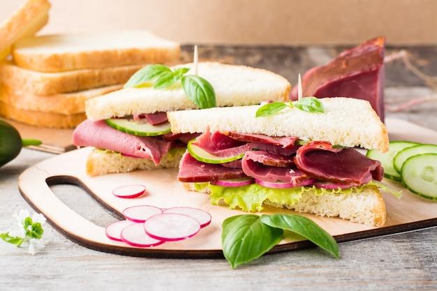 Frische sandwiches mit pastrami und gemüse auf einem schneidebrett. amerikanischer imbiss. rustikaler stil.