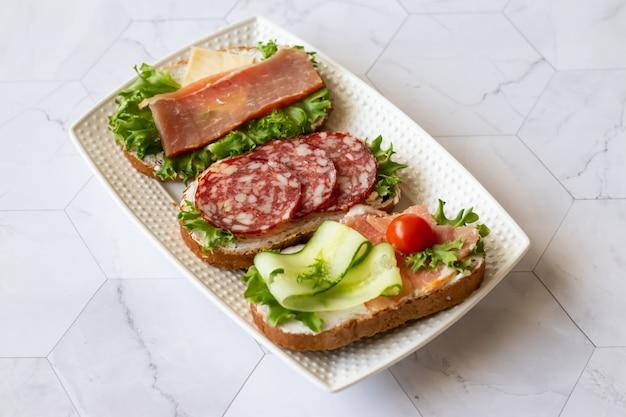 Frische sandwiches mit wurst, käse, speck, tomaten, salat, gurken auf marmor