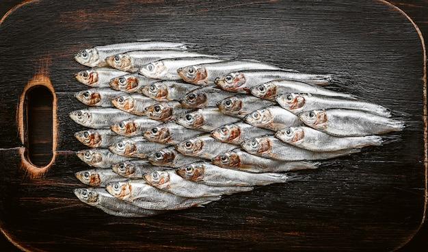 Frische sardelle und sprotte des rohen fisches auf einer holzoberfläche