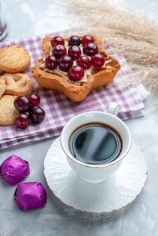 Frische sauerkirschen in teller mit sternförmigem cremigem kuchentee und keksen auf weiß
