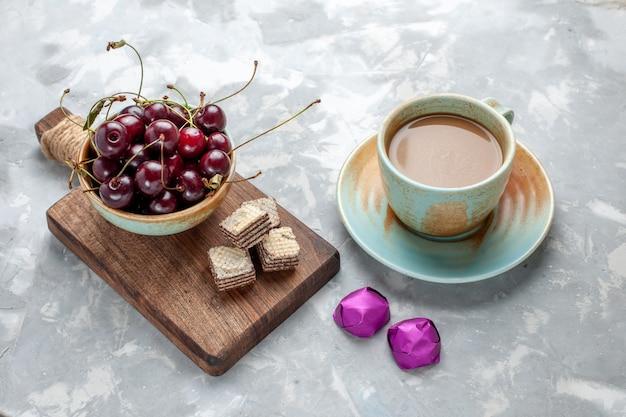 Frische sauerkirschen mit milchkaffee auf grauem schreibtisch, süßes fruchtwaffelfoto