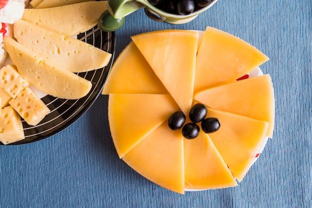 Frische scheiben käse und oliven auf teller