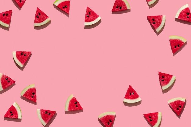 Frische scheiben wassermelone auf einem rosa hintergrund harte schatten der sonne. minimales konzept von reisen und urlaub mit kopienraum