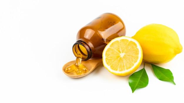 Frische scheibenzitrone mit blättern, vitamin- cergänzung vom natürlichen lokalisiert auf weiß