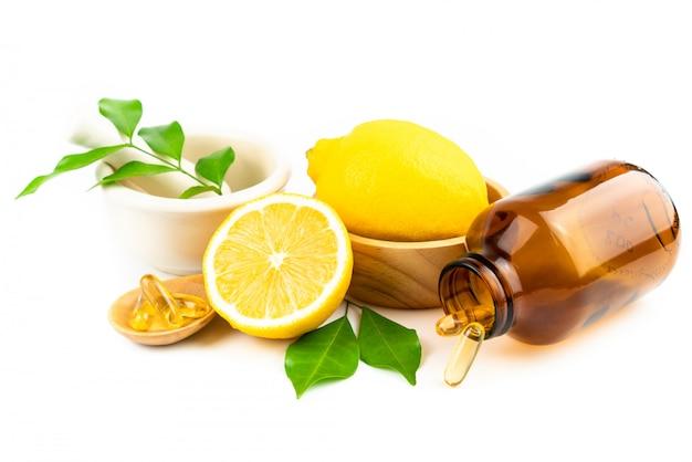 Frische scheibenzitrone mit blättern, vitamin- ckapselergänzung von natürlichem lokalisiert